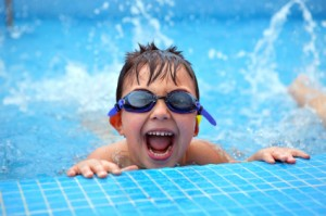 boy splashing in swimming pool